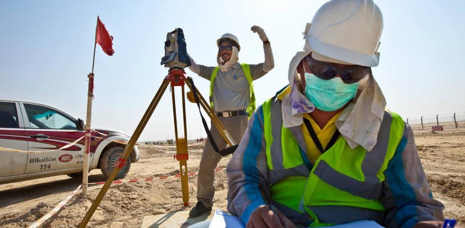 Géomètres travaillant devant le pipe rack. Construction de la raffinerie de Jubail en Arabie Saoudite. Satorp.