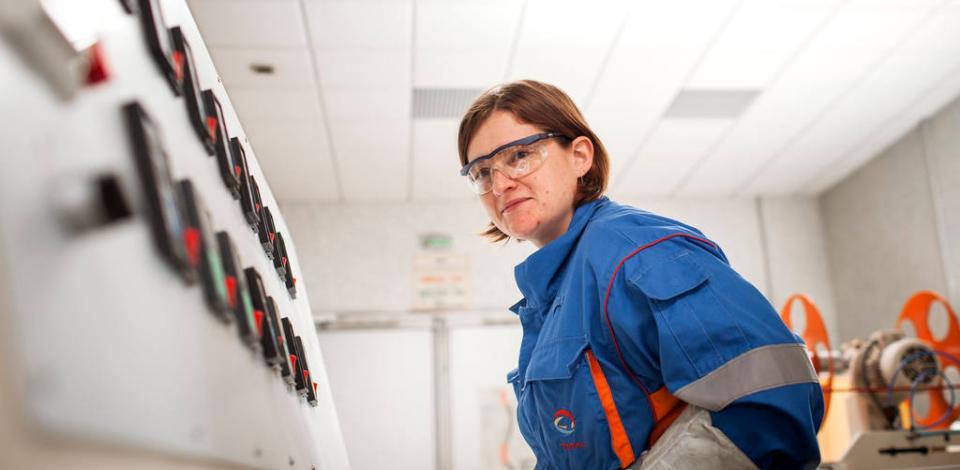Anne-Lise MAY, responsable du laboratoire PS, lors de l'extrusion d'un film de polystyrène et contrôle qualité du produit fini. Laboratoire d'analyse de polystyrène. Plateforme de Carling Saint-Avold, Moselle, France.