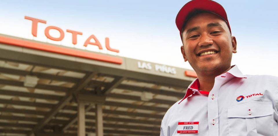 Un pompiste de la station-service Las Pinas. À l'arrière plan, le auvent de la station-service portant l'enseigne TotalEnergies.