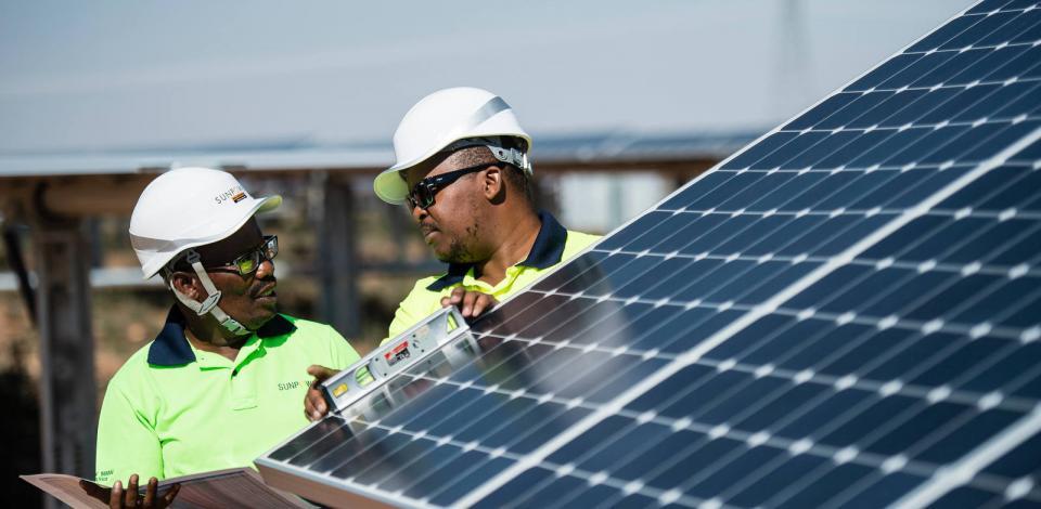 Opérateurs effectuant des réglages sur des panneaux. Centrale Solaire Sunpower TotalEnergies, Prieska.