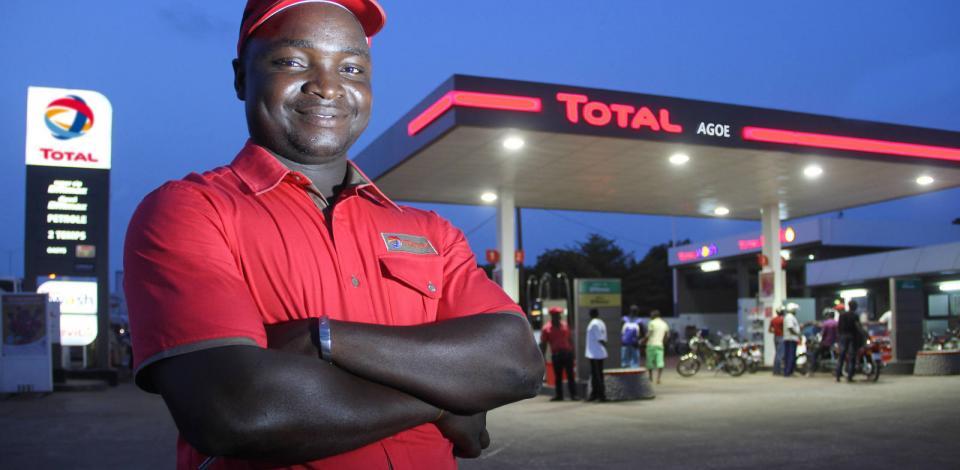 Un employé souriant à la station-service Agoe. À l'arrière plan, le auvent de la station-service et le totem carburant. Prise de vue réalisée en fin de journée, avec les éclairages de la station-service actifs.