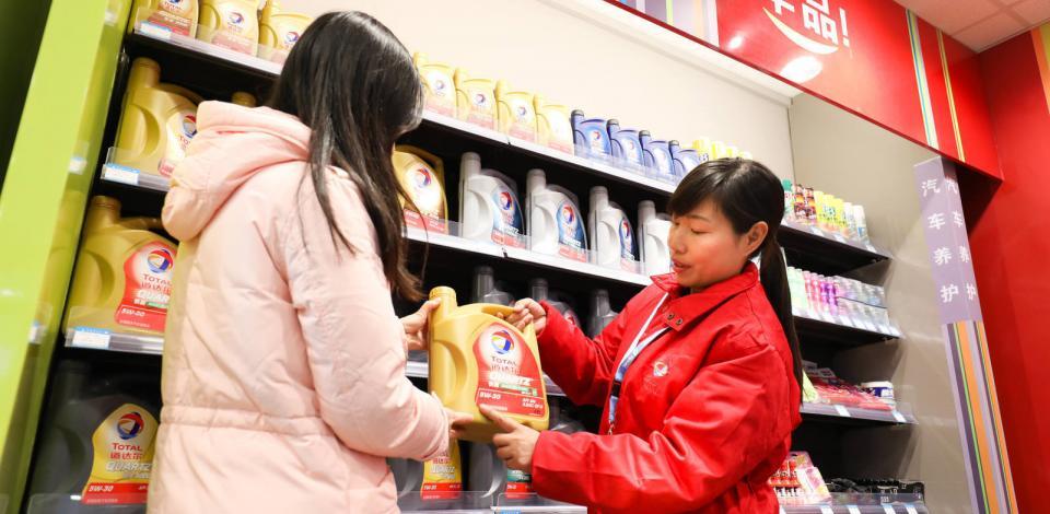 Station-service Total à Wuhan. Dans la boutique Bonjour, une employée aide une cliente dans le choix d'un lubrifiant Total.